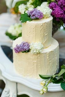 O bolo de casamento multinível com lilás em cima da mesa