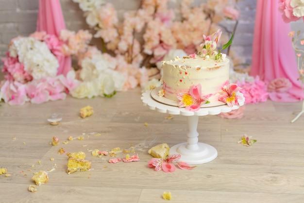 O bolo destruído com o creme branco e rosa em um aniversário da criança envelhece um ano