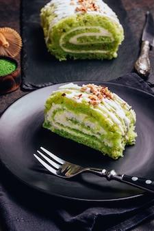 O bolo verde do matcha rola em uma placa preta.