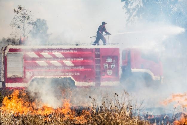 O bombeiro em chamas truk com mangueira extingue um incêndio
