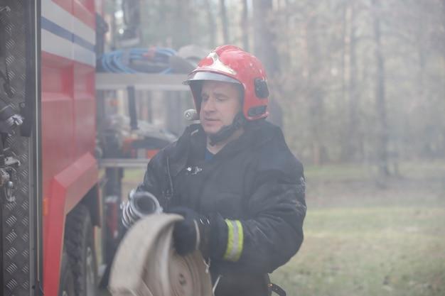 O bombeiro na fumaça desenrola as mangueiras. bombeiro na fumaça.