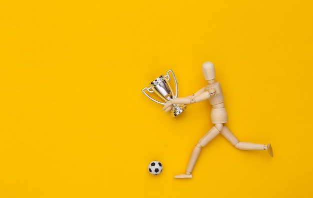 O boneco de madeira corre com a bola de futebol e a taça do campeonato em fundo amarelo