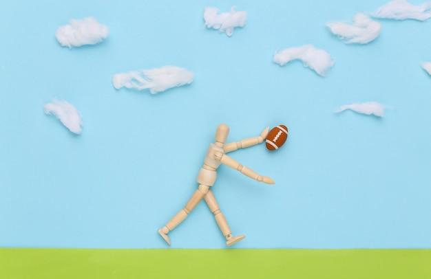 O boneco de madeira joga rúgbi com uma bola em um campo feito à mão no céu cheio de nuvens