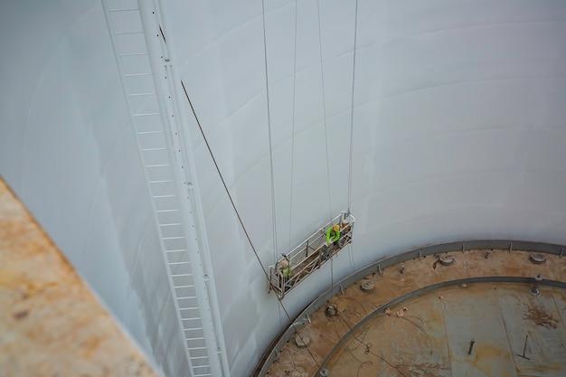 O boom do trabalhador masculino levanta o jato de areia no branco da placa interna do tanque.