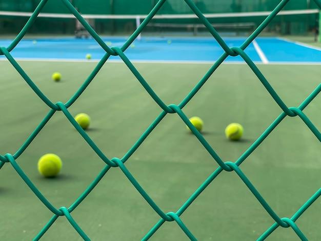 O borrão da bola de tênis na quadra olhando para a rede de ferro verde