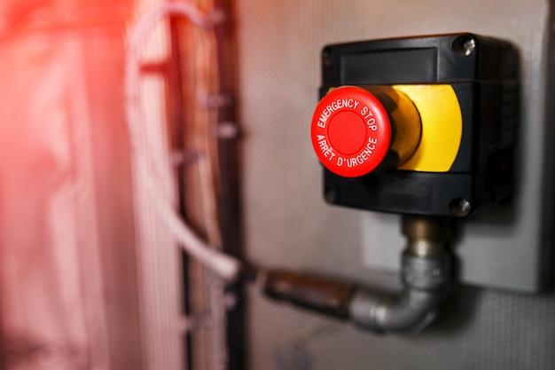 O botão vermelho de emergência ou o botão de parada para pressionar a mão. botão stop para máquina industrial