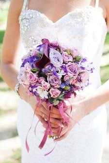 O bouguet de casamento com rosas lilás, eustoma e lírio nas mãos da noiva sobre vestido de noiva de renda branca