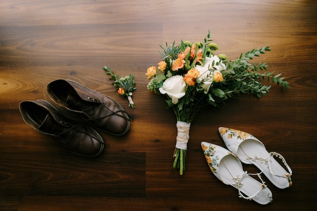 O bouquet da noiva com grandes rosas brancas e a flor da lapela do noivo