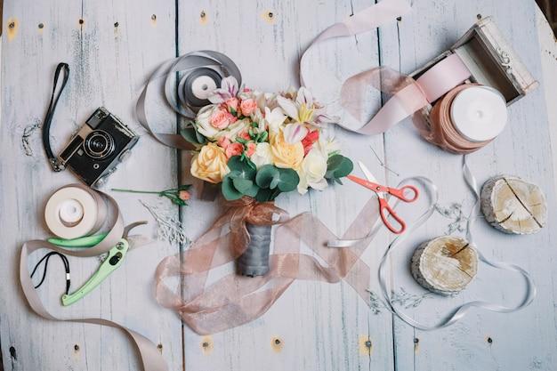 O bouquet de casamento está entre fitas, câmera e tesoura na t