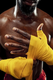 O boxeador afro-americano envolve as mãos com uma bandagem amarela