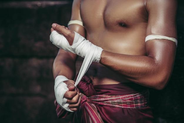 O boxeador estava sentado na pedra, amarrou a fita na mão, preparando-se para lutar.