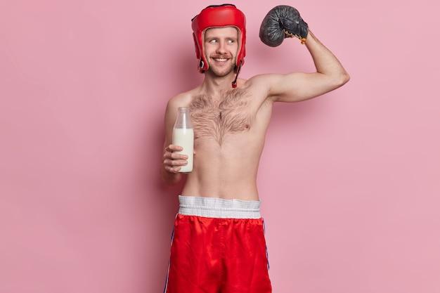 O boxeador magro e engraçado levanta o braço e mostra os músculos que desejam alcançar ótimas poses de resultado esportivo com o torso nu bebe leite