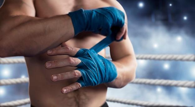 O boxeador puxa o curativo antes da luta ou do treinamento.