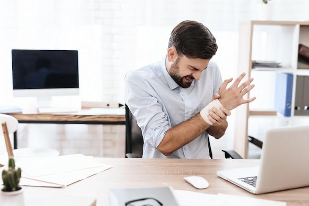 O braço de um homem dói. seu rosto está fazendo uma careta de dor.