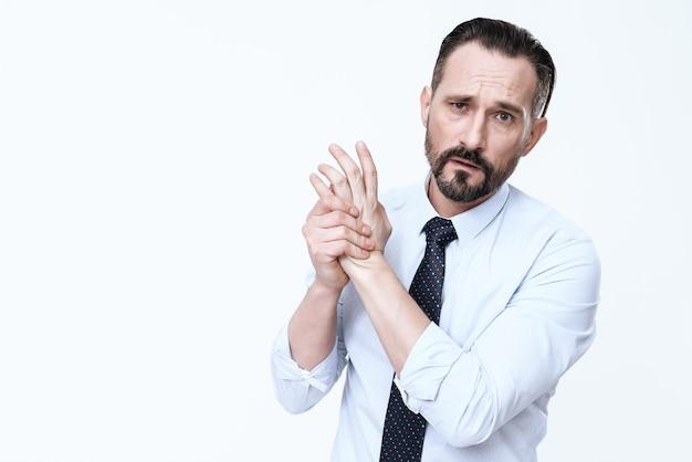 O braço de um homem está doendo. dói ele, ele sofre.