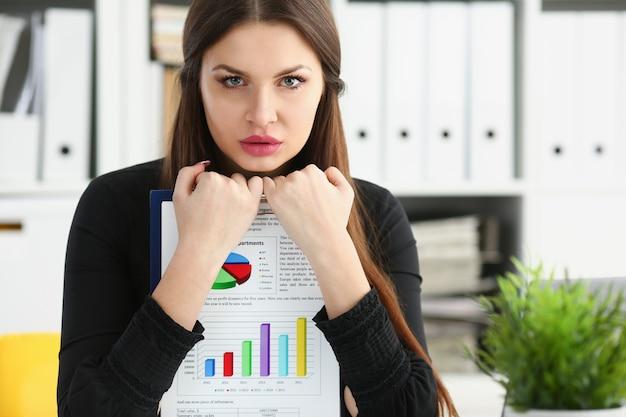 O braço feminino mostra o gráfico de estatísticas grampeado no retrato do escritório.