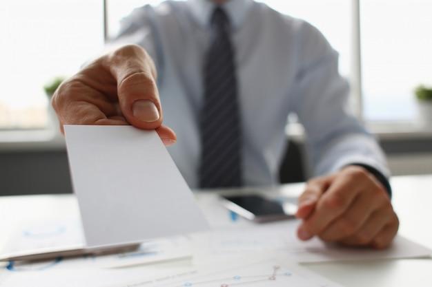 O braço masculino no terno dá o cartão de visita em branco ao visitante