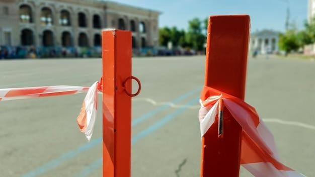 O branco vermelho não atravessa a fita e o poste de metal. sinalizador fita vermelha e branca pendurada em uma cerca de metal, perigo, advertência. fita e poste de metal vermelho. a fita proibida envolve uma área insegura.