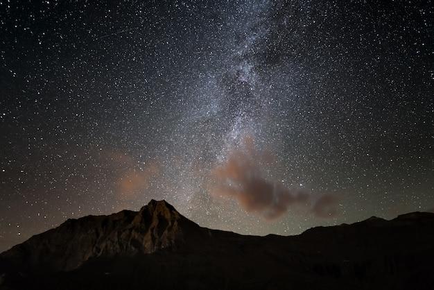 O brilhante colorido arco da via láctea e o céu estrelado do alto dos alpes