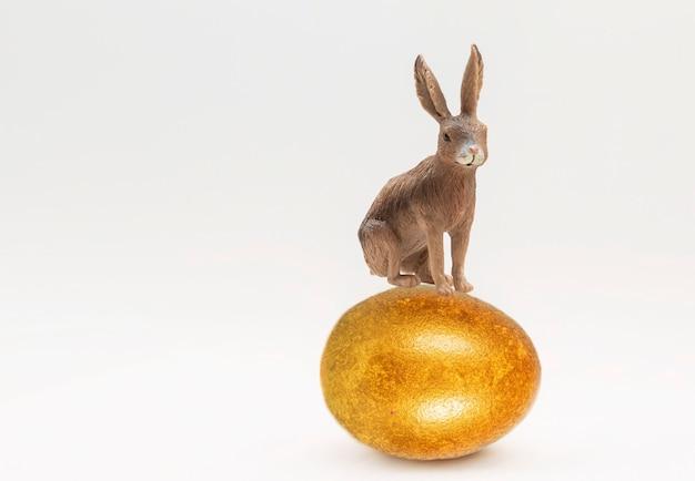 O brinquedo do coelhinho da páscoa fica em um ovo de ouro isolado em um fundo branco.