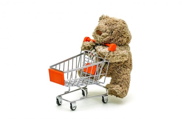 O brinquedo isolado do urso de peluche está empurrando o carro do trole