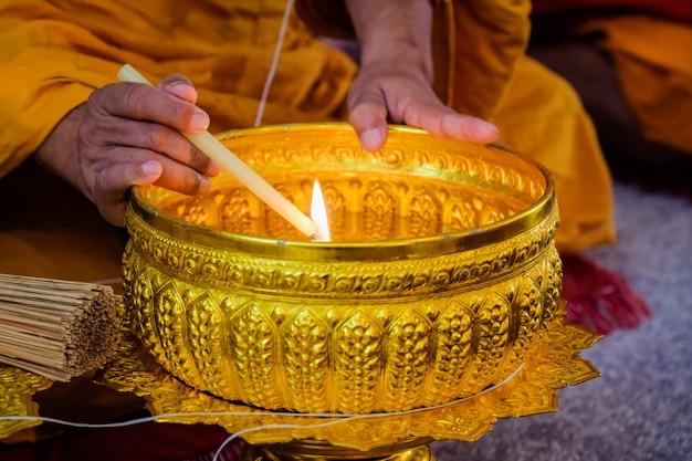 O buda está queimando velas para fazer água benta.