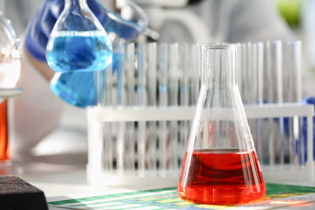 O bulbo da indústria química com os tubos líquidos cor-de-rosa magenta azuis do laboratório está em cima da mesa no laboratório de substâncias de desenvolvimento de teste de teste líquido envenena aditivos estabilizadores sabores limpeza da casa.