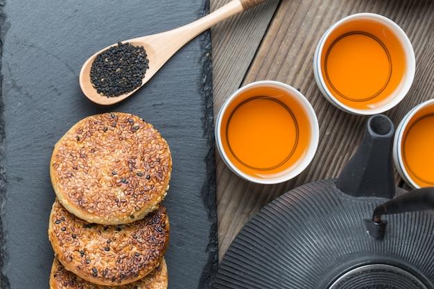 O bule e chá sobre a mesa de madeira, deliciosos petiscos