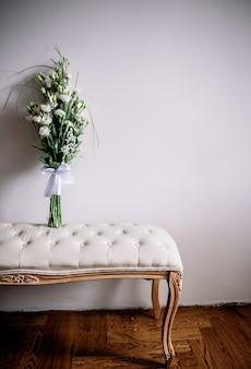 O buquê branco macio fica em um pequeno sofá