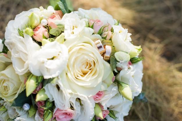 O buquê da noiva com flores brancas e anéis na grama