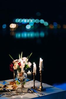 O buquê da noiva na mesa com velas em castiçais.