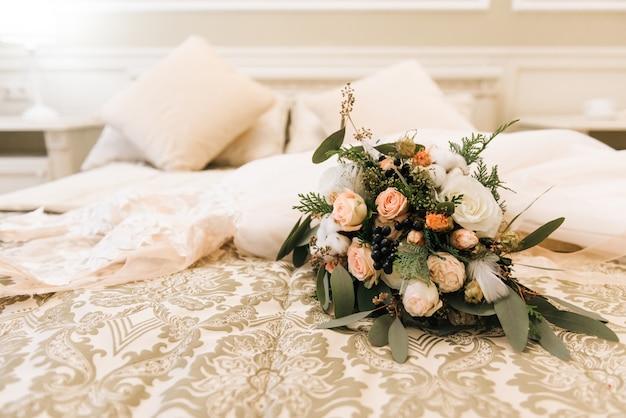 O buquê de noiva de inverno com rosas, algodão e abetos encontra-se ao lado do vestido de noiva em um luxuoso quarto de hotel