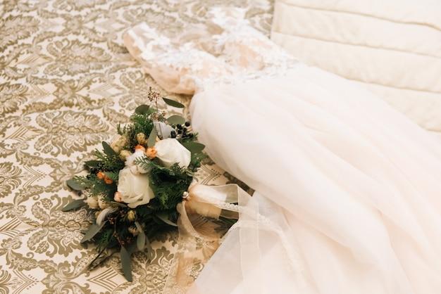 O buquê de noiva de inverno com rosas, algodão e abetos encontra-se ao lado do vestido de noiva em um luxuoso quarto de hotel Foto Premium