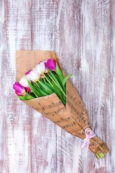 O buquê de tulipas é embrulhado em um papel isolado em um fundo de madeira
