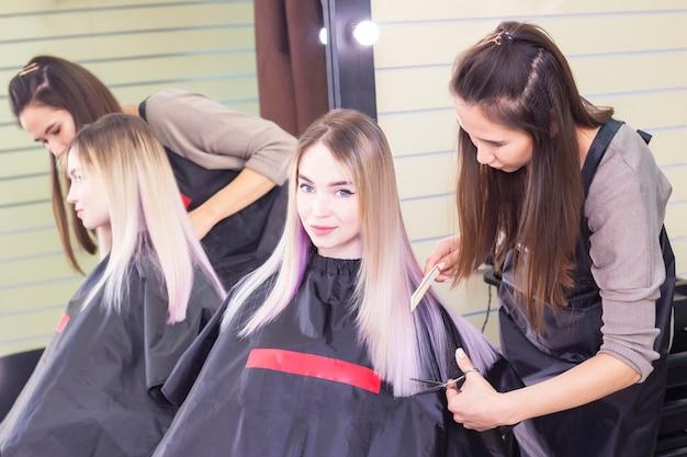O cabeleireiro corta o cabelo de uma menina com uma tesoura. garota em um salão de beleza, cuidados com os cabelos