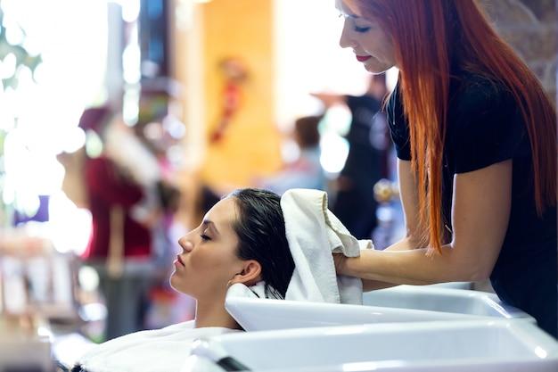 O cabeleireiro envolve o cabelo do cliente em uma toalha após a lavagem.