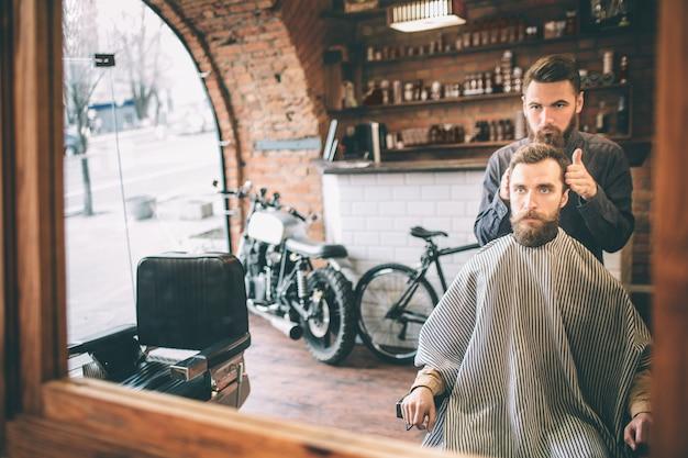 O cabeleireiro está de pé nas costas e modelando o cabelo do seu cliente. o cliente está sentado na cadeira e olhando diretamente para o espelho.