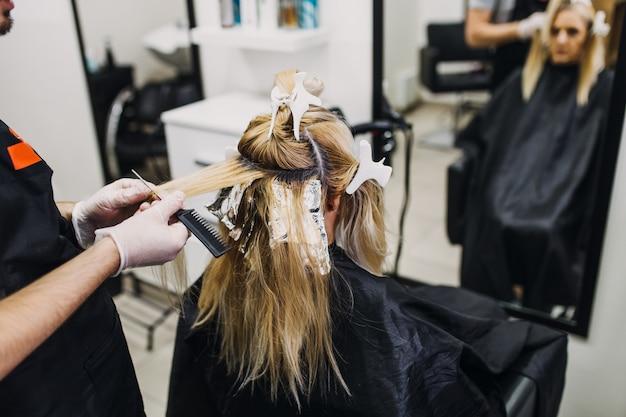 O cabeleireiro está tingindo o cabelo feminino, fazendo mechas de cabelo para sua cliente com um papel alumínio.