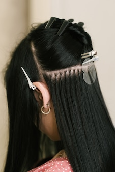 O cabeleireiro faz extensões de cabelo em uma jovem em um salão de beleza