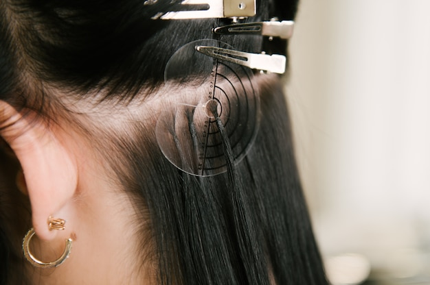 O cabeleireiro faz extensões de cabelo para uma jovem em um salão de beleza
