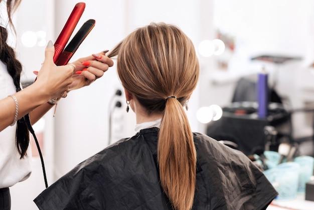 O cabeleireiro faz um penteado para uma mulher com cabelos longos castanhos claros