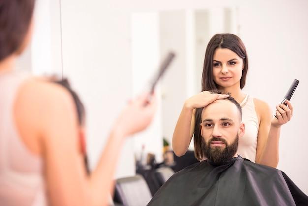 O cabeleireiro fêmea feliz está cortando o cabelo dos clientes no salão de beleza.