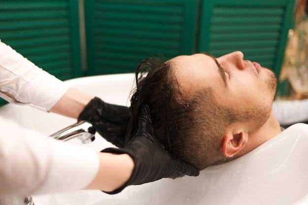 O cabeleireiro lava o cabelo de um cliente antes de cortar. homem bonito sério lava a cabeça em um salão de beleza