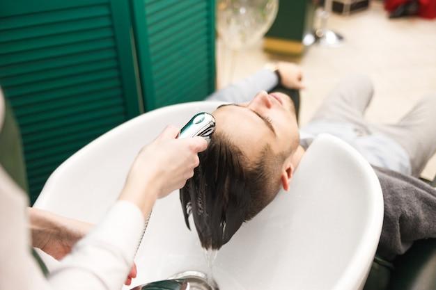 O cabeleireiro lava o cabelo de um cliente antes de cortar