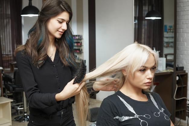 O cabeleireiro penteia os cabelos compridos do cliente