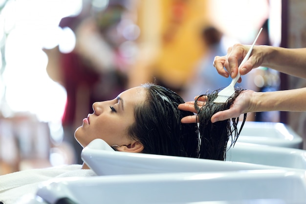 O cabeleireiro que aplica tratamento de cabelo para o cliente em um salão de beleza.