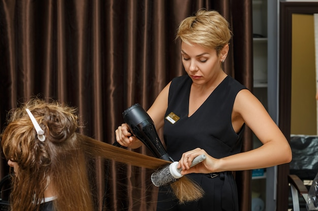 O cabeleireiro seca o cabelo para o cliente com um secador de cabelos.
