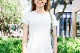 O cabelo marrom longo da menina asiática do moderno no t-shirt vazio branco está estando no meio da rua. Um fem