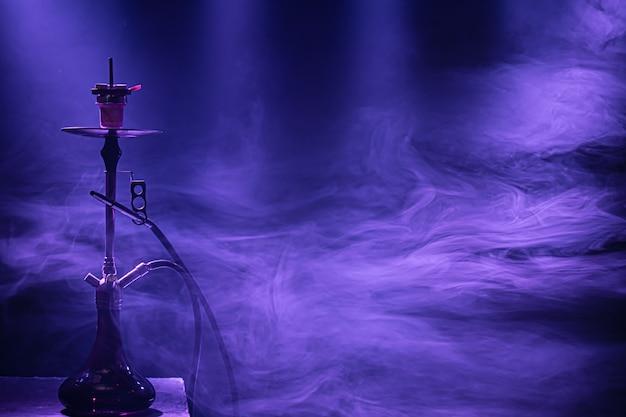 O cachimbo de água clássico com raios coloridos de luz e fumaça.