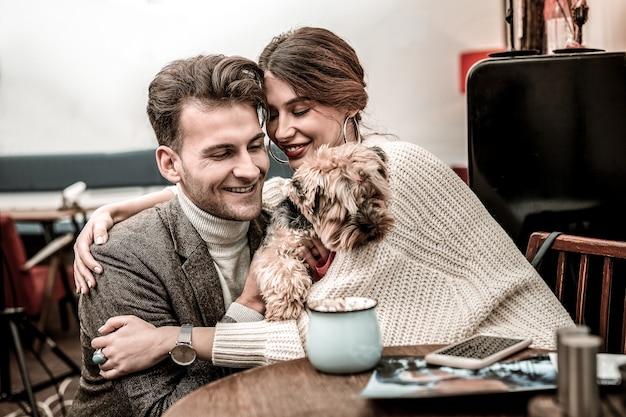O cachorro como parte da família. casal alegre abraçando seu novo animal de estimação
